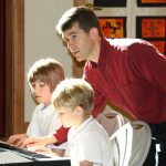 Mike Sakash teaches two young students on the keyboard