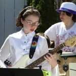 Students performing outdoors on guitar and drums