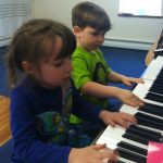 Two preschoolers play piano together