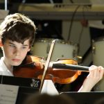 A young boy plays violin