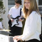 Two youth students perform outdoors on guitar and keyboard
