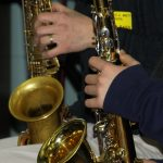 A detail of two saxophone players' instruments and hands