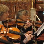 Three women play violin together