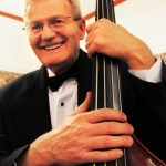 An older man smiling while holding his upright bass